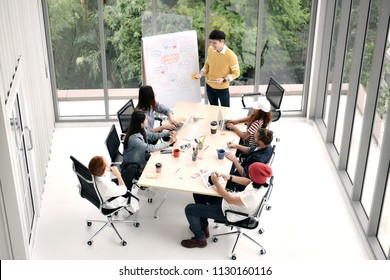 Group of business persons sitting around a desk listening to and discussing about a presentation by a colleague at the office
