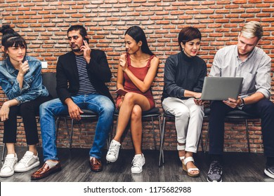 Group of business sitting relax use technology together of smartphone and laptop computer checking social apps and working on brick wall background.Communication concept