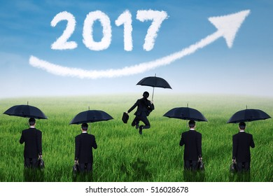 Group of business team with black umbrella on the meadow while looking at cloud shaped number 2017 and upward arrow on the blue sky