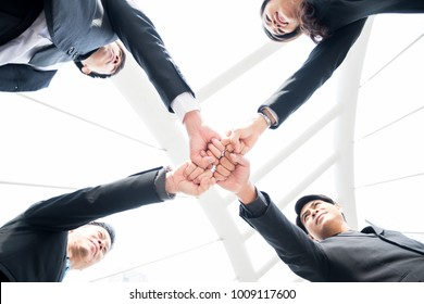 A group of business team making a fist bump together. Teamwork and powerful cooperate at the city. bottom view