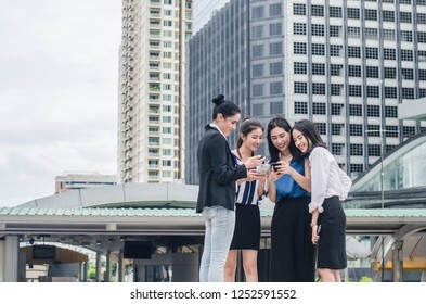 A group of business women looking at a cell phone and laughing in the street with office buildings in the background