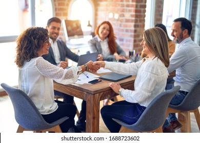 幸せで自信に満ちた笑顔を見せるビジネスワーカーのグループ。オフィスで笑顔で握手を交わしながら働く