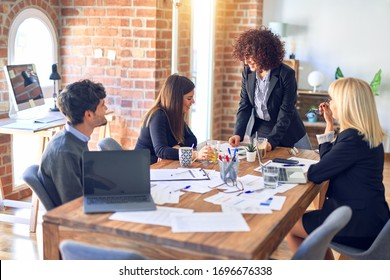 Group of business workers smiling happy and confident. Working together with smile on face. Young beautiful woman standing explaining documents at the office