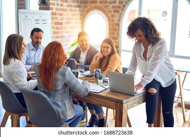 Group of business workers working together. Middle age beautiful businesswoman standing smiling happy looking at the camera at the office
