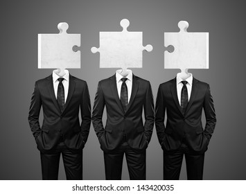 group of businessman with puzzle pieces instead heads