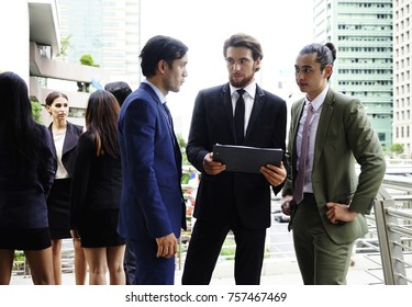 The group of businessman with suit  standing and talking together. The group of  working woman talking in the background with city view.