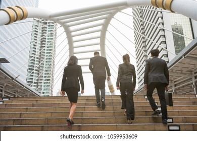 Group of businessmen and businesswomen with full business suit walking upstair in modern city with business buildings background. Teamwork business concept.