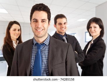 A group of businessmen and businesswomen in an office environment, their leader is on the front