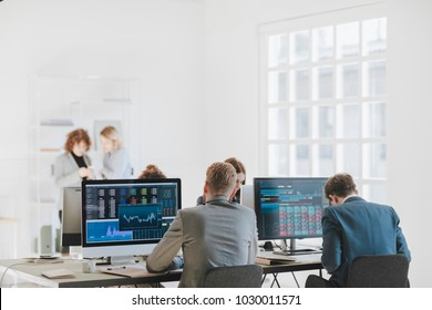 Group of businessmen and businesswomen stock brokers working at office.