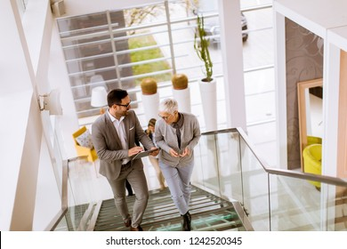 Group of businessmen and businesswomen walking and taking stairs in an office building