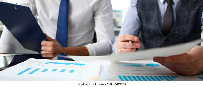 Group of businessmen with financial graph and silver pen in arm solve and discuss problem with colleague closeup. Situation examination at board council sale adviser job stock exchange market profit