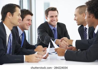Group Of Businessmen Having Meeting In Office
