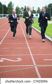 Group of businessmen running on a track. How's gonna win?