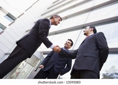 Group of businessmen shaking hands outside modern office
