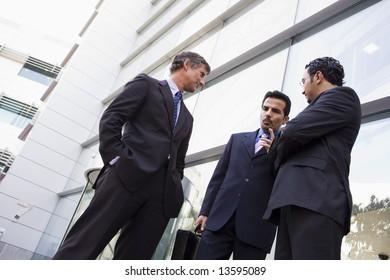 Group of businessmen talking outside modern office