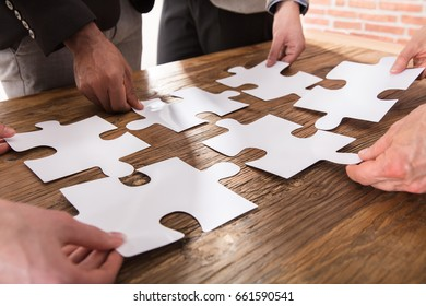 Group Of Businesspeople Arranging The Puzzle On Wooden Table