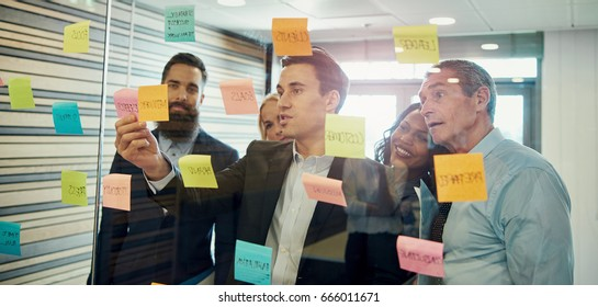 Group of businesspeople brainstorming, putting sticky note on glass