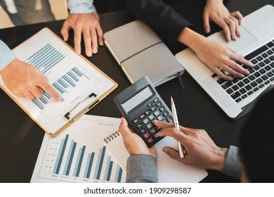 Group of businesspeople busies discussing financial Business people brainstorming at office desk, they are analyzing financial reports and pointing out financial data on a sheet