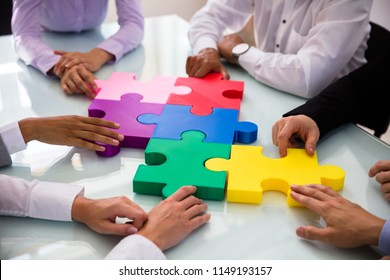 Group Of Businesspeople Colorful Solving Jigsaw Puzzle On Desk In Office