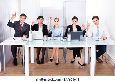 Group Of Businesspeople In Conference Raising Hands