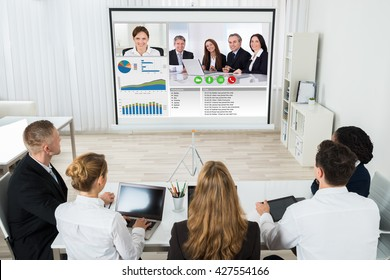 Group Of Businesspeople Discussing Graphs Through Videochat In Office
