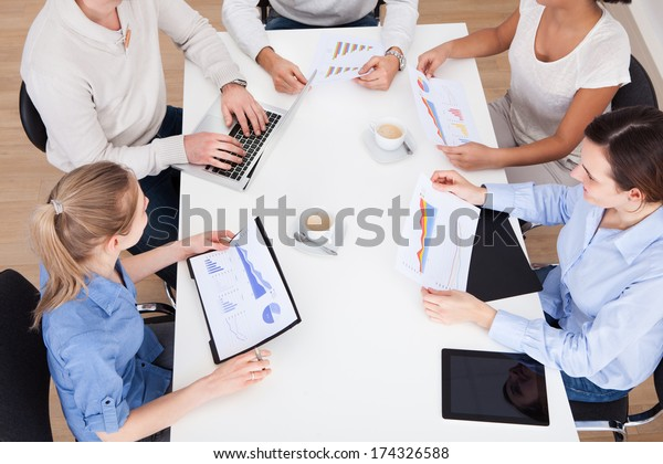 Group Of Businesspeople Discussing On Graph In Meeting