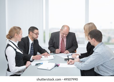 Group of businesspeople formed of men and women in an office at a table. Two of them sign a contracts.