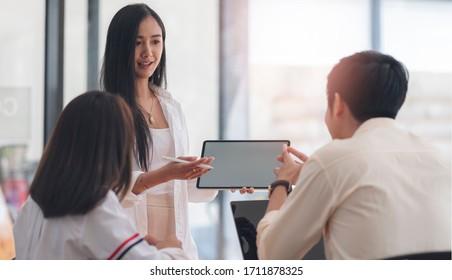 Gruppe von Geschäftsleuten, die sich treffen und über Geschäftspläne im modernen Büro diskutieren, junge Geschäftsleute, die Tablet-Geschäftspläne mit ihrem Team im Amt vorstellen.