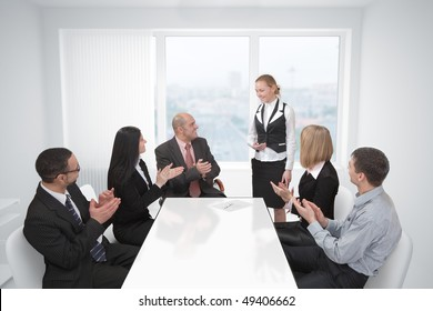 Group of businesspeople in office applaud a colleague.