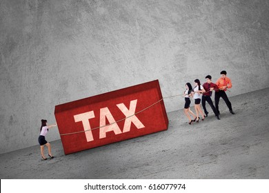 Group of businesspeople pulling a boulder with a tax word. Concept of Tax