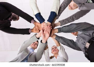 Group Of Businesspeople Putting Their Hands On Top Of Each Other Against White Background