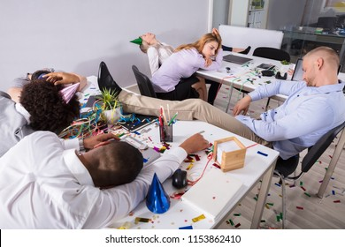 Group Of Businesspeople Sleeping In Office After New Year Party