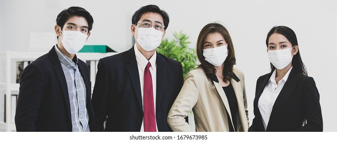 Group of businesspeople team in office wearing surgical hygienic protective mask on face standing and looking to camera, idea for prevent crisis of coronavirus and health care for workers employees