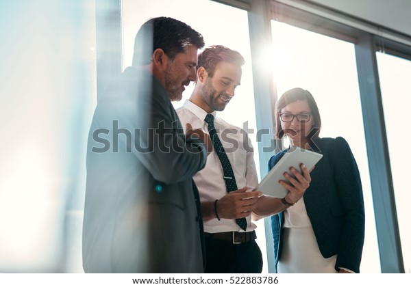 Group of businesspeople using a digital tablet together in front of office building windows overlooking the city