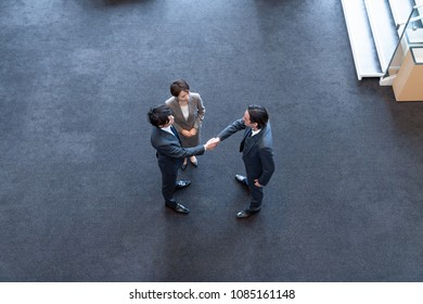 Group of businessperson shaking hands in the hall.
