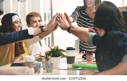 Group of businesspersons tapping hands / hive fiving in agreement in a meeting at office