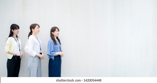 Group of businesswoman standing in front of a wall.