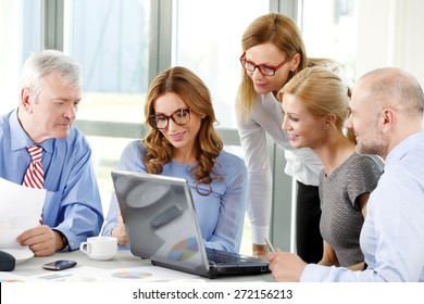 Group of businesswomen and businessmen sitting around conference table and working on presentation at laptop. Teamwork at office.