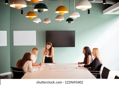 Group Of Businesswomen Sitting Around Boardroom Table And Collaborating On Task At Graduate Recruitment Assessment Day