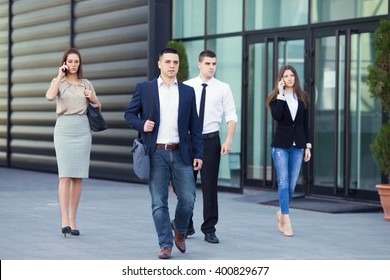 Group of busy business people on the move in front of the office building. Focus on confident young man walking down the street