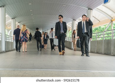 Group of busy business people on the move in overpass bridge. Focus on confident young man walking down the street