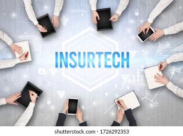 Group of Busy People Working in an Office with INSURTECH inscription, modern technology concept