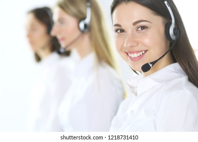 Group of call center operators at work. Focus at beautiful business woman in headset