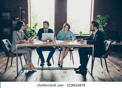 Group of calm professional banker broker economist employee employer sit behind wooden table discuss offer from main office indoor loft interior