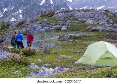 A group of camp tents stands on rocks, amid high mountains and snow-capped peaks. Twilight, night. A group of tourists are resting.