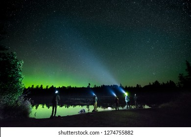 A group of campers stand if front of a tranquil lake looking up towards the norther lights with their headlamps on.