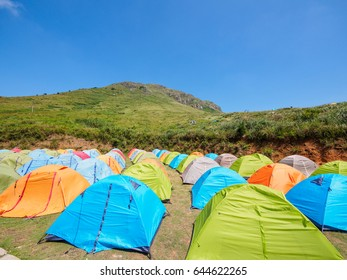 Group of camping tents near mountain river in the summer.