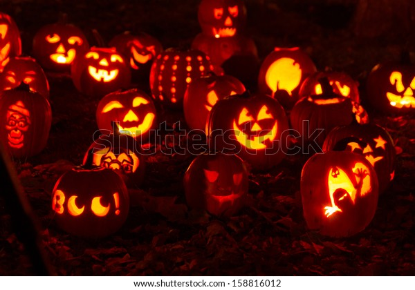 Group of candle lit Halloween pumpkins in park on fall evening