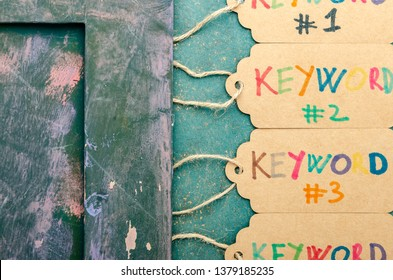 "A group of cardboard label tags showing a sequence of the word ""keyword"" in several colours next to a hand-painted photo frame"