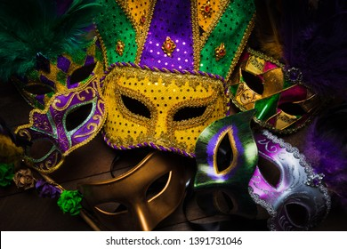 A group of carnivale or mardi gras mask with a yellow jester on a dark background